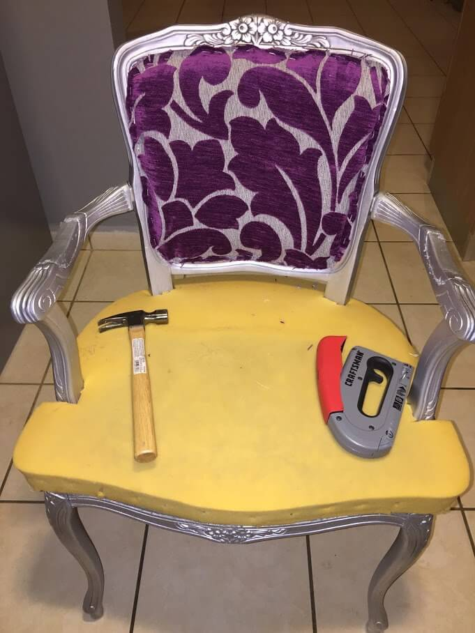 small victorian arm chair with a hammer and stapler on top if it