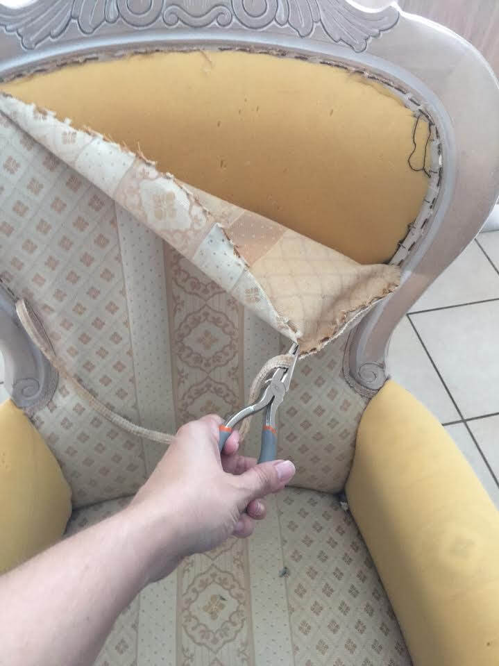 hand removing the fabric of a victorian arm chair to reupholster it