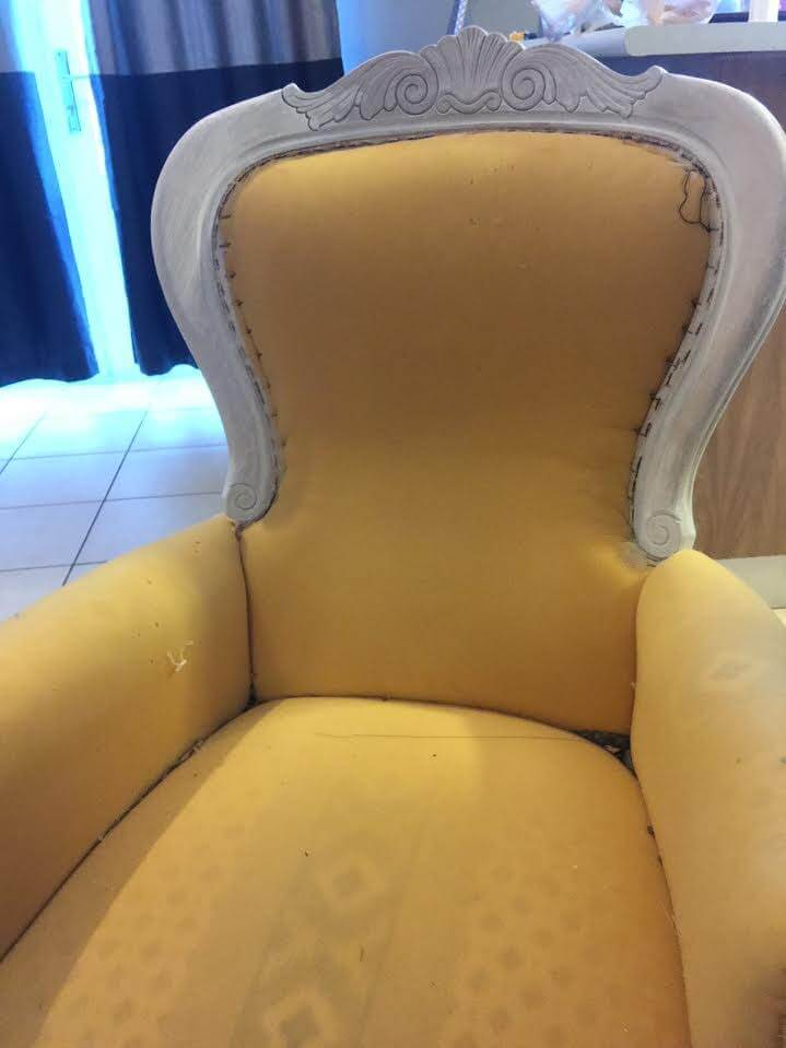 victorian arm chair with exposed foam and a white primer on its frame