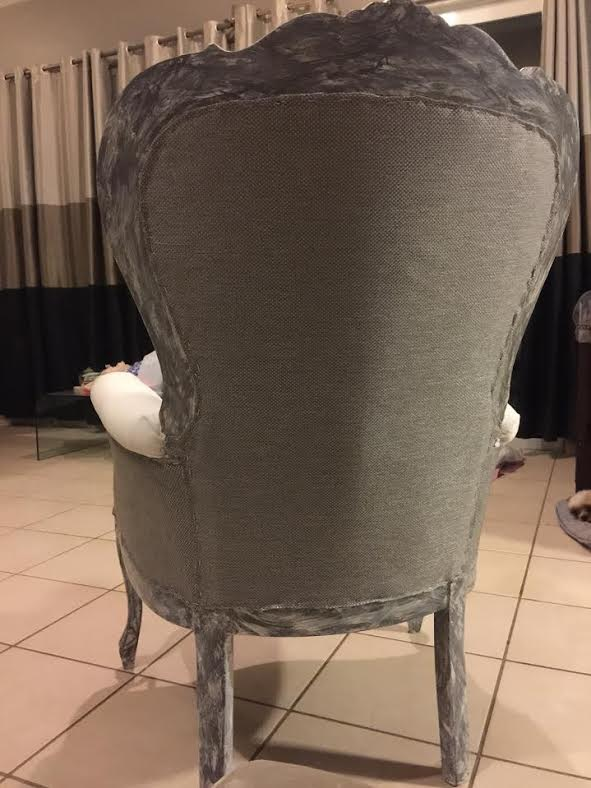 back of a victorian chair upholstered with gray fabric