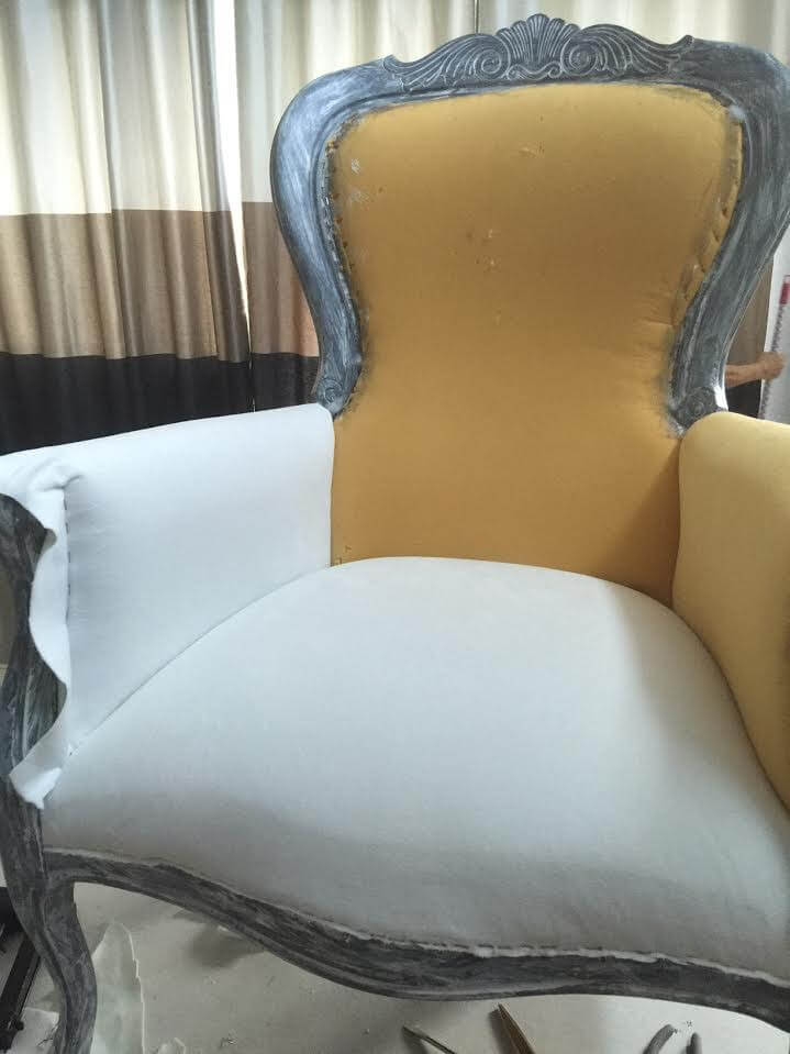 beginning of upholstery process of a victorian arm chair using a white fabric